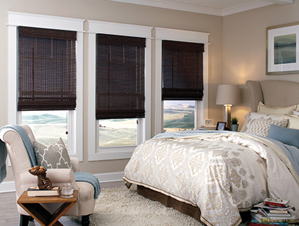 Room scene displaying three walnut natural Roman shades in a bed room