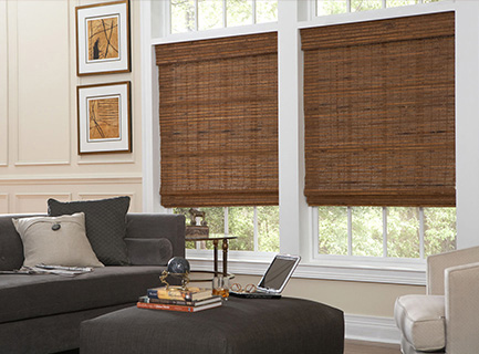 Room scene depicting two cordless, oak woven wood shades in the living area of a house