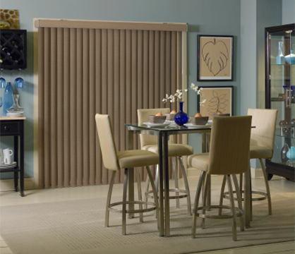room scene showing brown fabric vertical blinds over a patio door in a dining room