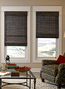 Vignette showing two grey natural Roman shades in a living room